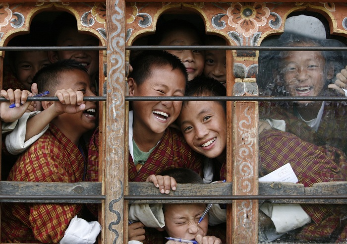 PhotoFly Travel Club | School children react to the camera through the window of their classroom in a school in Thimphu | PhotoFly Travel Club